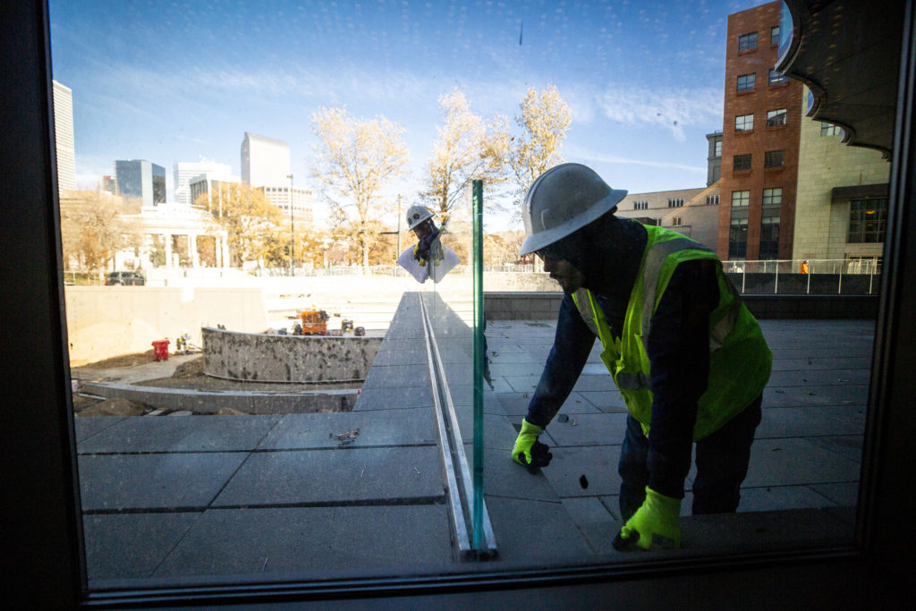 Workers fit glass outside of the Denver Art Museum's new Martin Building during construction, Nov 13, 2019. (Kevin J. Beaty/Denverite)