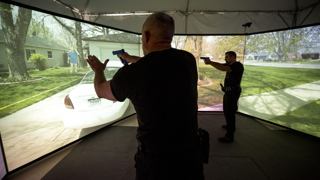 Two Denver Police officers run through a suicide scenario inside the Denver Police Academy's VirTra virtual reality training system, Nov. 13, 2019. (Kevin J. Beaty/Denverite)