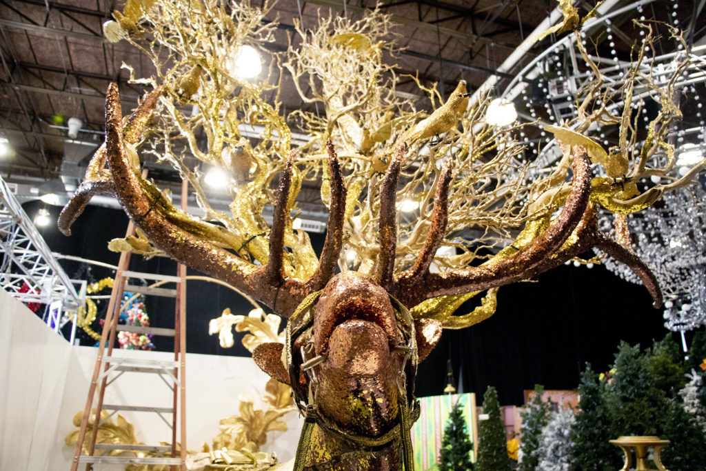 """Here is a shiny elk. Lonnie Hanzon's """"Camp Christmas"""" is under construction at Stanley Marketplace. Nov. 15, 2019. (Kevin J. Beaty/Denverite)"""