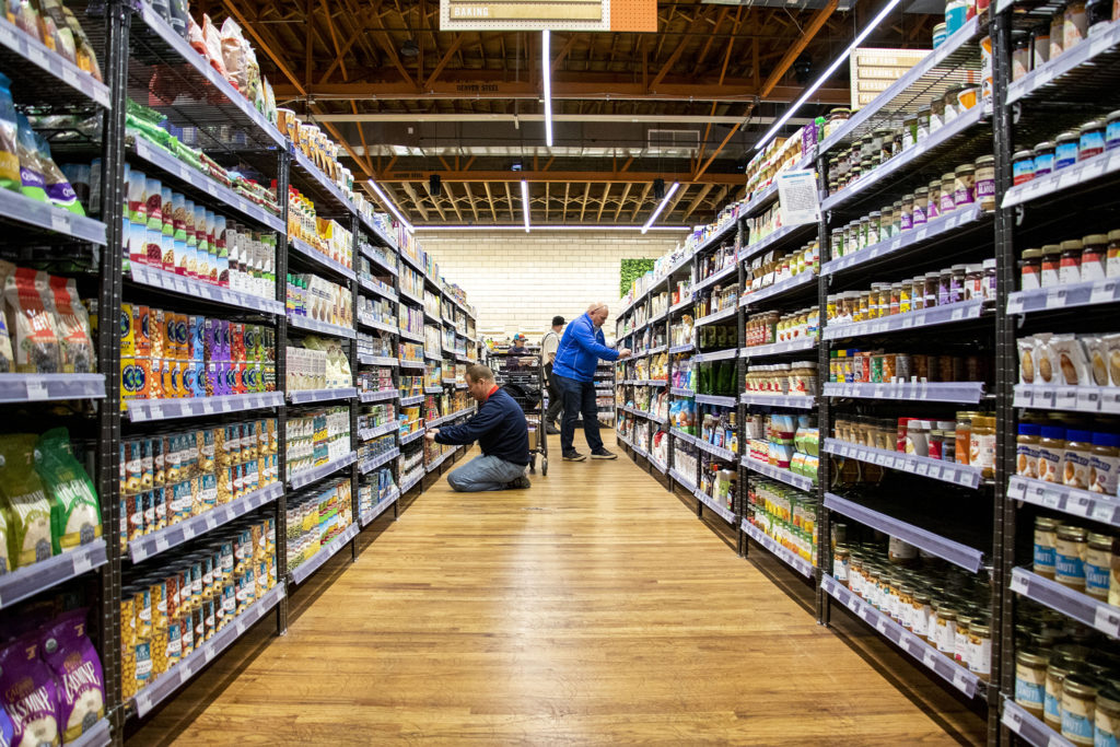 KeHE reps Jim Farrar and Ed Kitterman stock shelves at Leevers Locavore Northside before its grand opening. Nov. 20, 2019. (Kevin J. Beaty/Denverite)