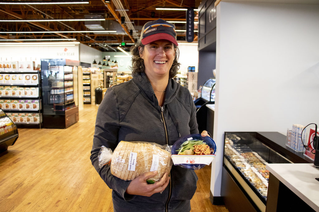 Andrea Salzberg holds bread and sushi she's getting ready to buy at Leevers Locavore Northside before its grand opening on 38th Avenue, Nov. 20, 2019. (Kevin J. Beaty/Denverite)