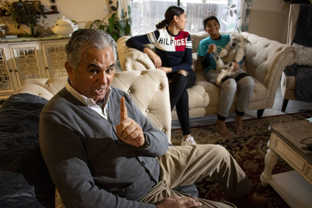 Raad Altaee speaks to a reporter inside his Montbello home as his kids – daughter Rasha, son Idrees and puppy Benji – hang out on the couch behind him. Nov. 21, 2019. (Kevin J. Beaty/Denverite)