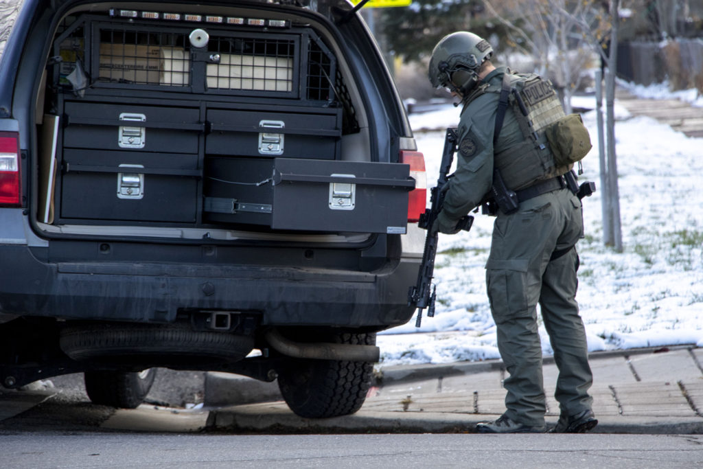 A Denver Police officer packs up after a standoff with a suspect on Humboldt Street near Cole Arts and Sciences Academy. Nov. 22, 2019. (Kevin J. Beaty/Denverite)