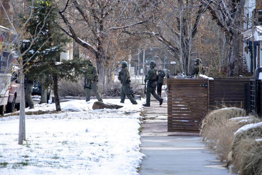 Denver Police walk away from a house on Humboldt Street after a standoff with a suspect near Cole Arts and Sciences Academy. Nov. 22, 2019. (Kevin J. Beaty/Denverite)