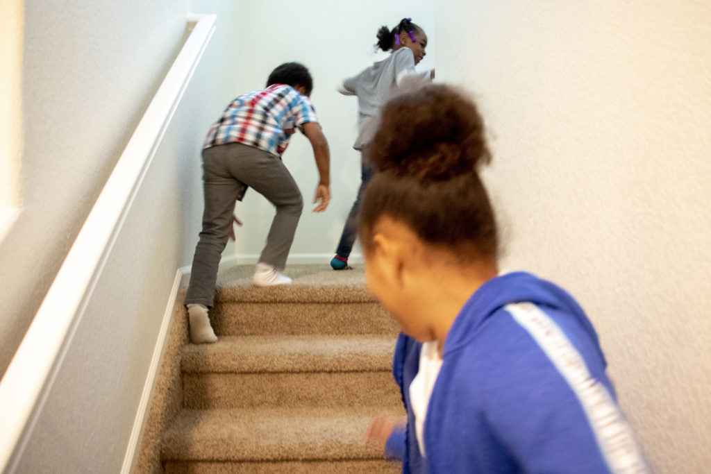 Mele Lavaka's boyfriend's kids, Na'Lonnie, Dedric and KyLani run up the stairs in her new home in Lochbuie, Colorado. Nov. 28, 2019. (Kevin J. Beaty/Denverite)