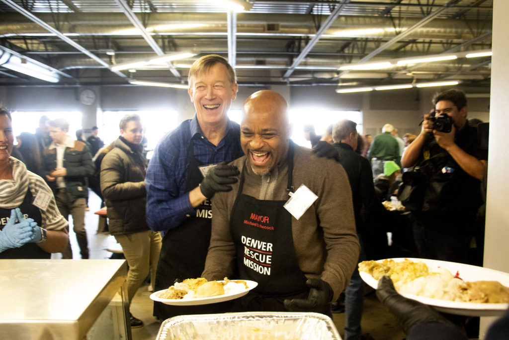 Former Gov. John Hickenlooper and Mayor Michael Hancock joke as Kyle Clark hands out meals during a Thanksgiving feast at the Denver Rescue Mission, Nov. 27, 2019. (Kevin J. Beaty/Denverite)