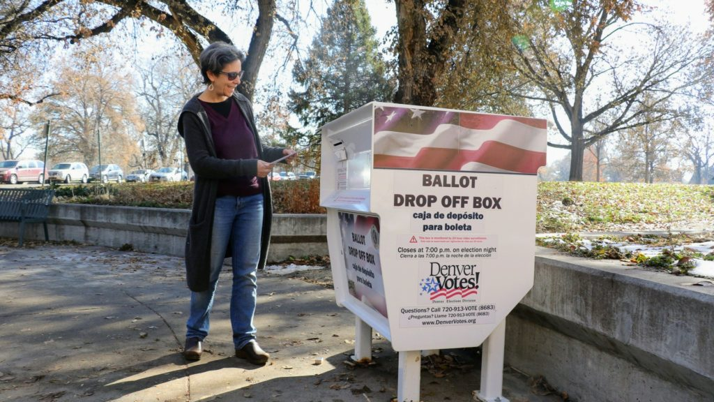 Jessica Cohen casts her ballot at a drop box in Washington Park. Nov. 5, 2019. (Kevin J. Beaty/Denverite)