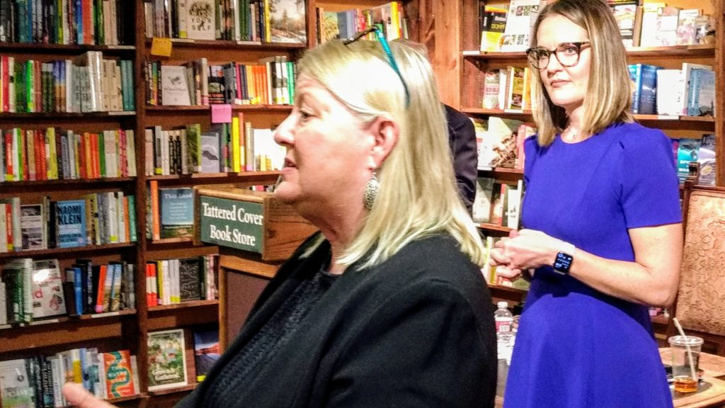 Jamie Rife in blue listens as Barbara Jackson describes her childhood experience of homelessness at the Nov. 17, 2019 launch of a book to which they both contributed. (Donna Bryson/Denverite)