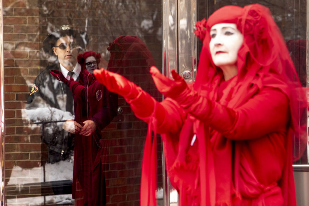 """The """"Red Brigade,"""" protesting Black Friday consumerism with Extinction Rebellion, forced Cherry Creek Mall security to lock some doors to prevent them from entering, Nov. 29, 2019. (Kevin J. Beaty/Denverite)"""