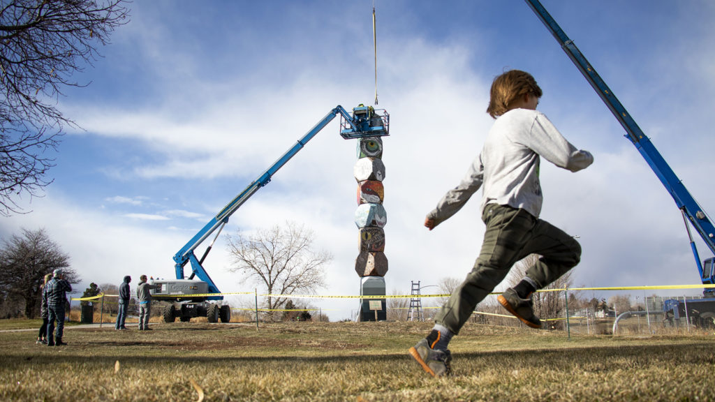 """The final piece in Jaime Molina's """"La Veleta/The Weathervane"""" is installed above Federal Boulevard from its new home at Barnum Park. Dec. 14, 2019. (Kevin J. Beaty/Denverite)"""