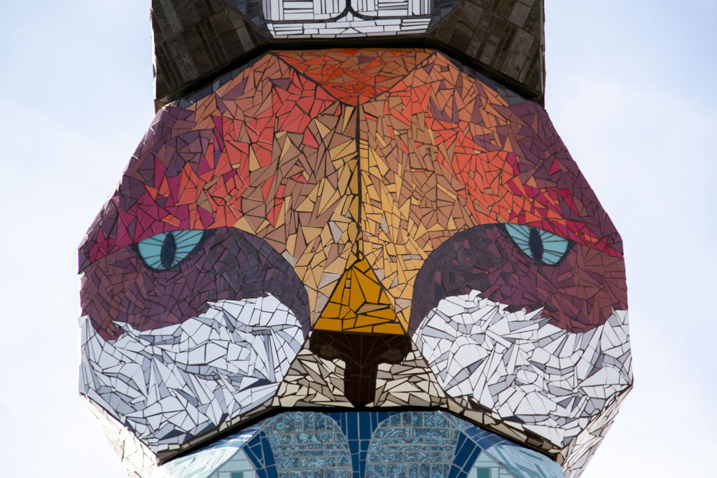 """A fox face in Jaime Molina's """"La Veleta/The Weathervane"""" towering above Federal Boulevard from its new home at Barnum Park. Dec. 14, 2019. (Kevin J. Beaty/Denverite)"""