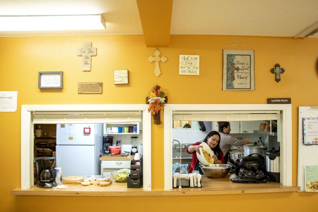 Maria Gueta and Cleme Rodriguez work in Ministerio Hispano Presbyterian Church's kitchen in preparation for Kim Ramos' quinceañera party, Dec 14, 2019. (Kevin J. Beaty/Denverite)