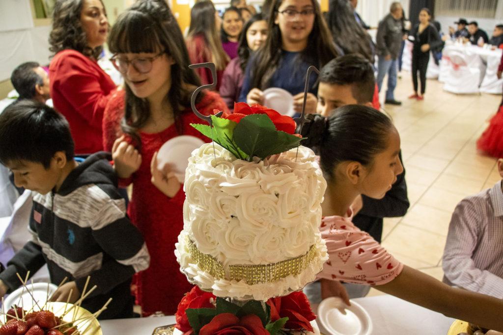 Kids dig into candy and chocolate before Kim Ramos' fancy quinceañera cake was cut. Ministerio Hispano Presbyterian Church, Dec 14, 2019. (Kevin J. Beaty/Denverite)