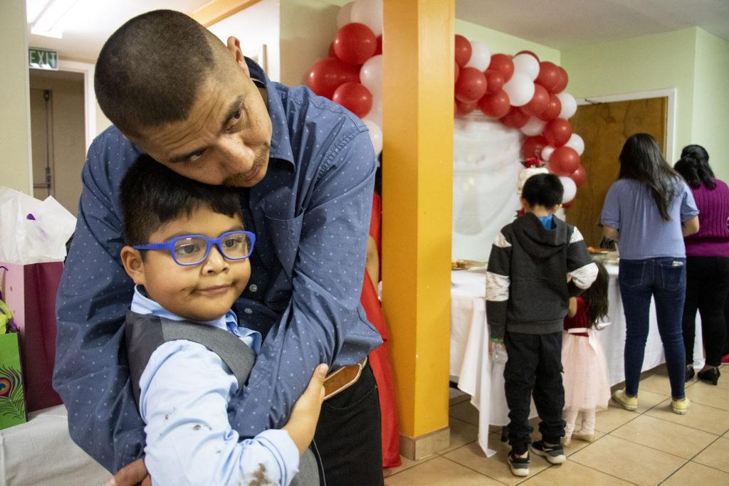Fernando Piedra embraces his son, Ian, during the quinceañera of his step-daughter, Kim Ramos. Ministerio Hispano Presbyterian Church, Dec 14, 2019. (Kevin J. Beaty/Denverite)