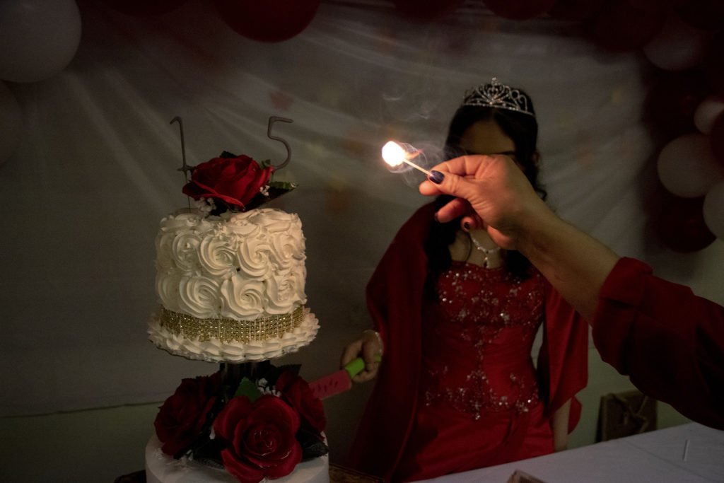 Kim Ramos prepares to cut her cake during her quinceañera celebration in the basement of Ministerio Hispano Presbyterian Church, Dec 14, 2019. (Kevin J. Beaty/Denverite)