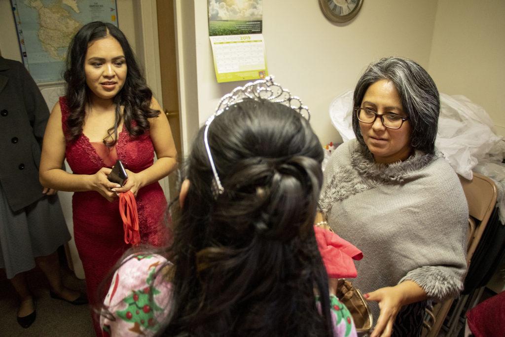 Kim Ramos' mother, Erika Piedra Avendaño (left), and a member of her church, Delfina Solano, inspect Ramos' makeup before her quinceañera ceremony at Ministerio Hispano Presbyterian Church, Dec 14, 2019. (Kevin J. Beaty/Denverite)