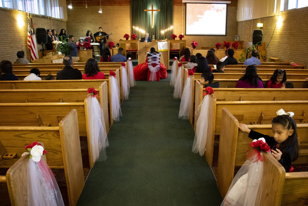 Kim Ramos sits in a chair adorned with lace as Pastor Rafael Ballares addresses the crowd in Spanish. Ramos' quinceañera at Ministerio Hispano Presbyterian Church, Dec 14, 2019. (Kevin J. Beaty/Denverite)