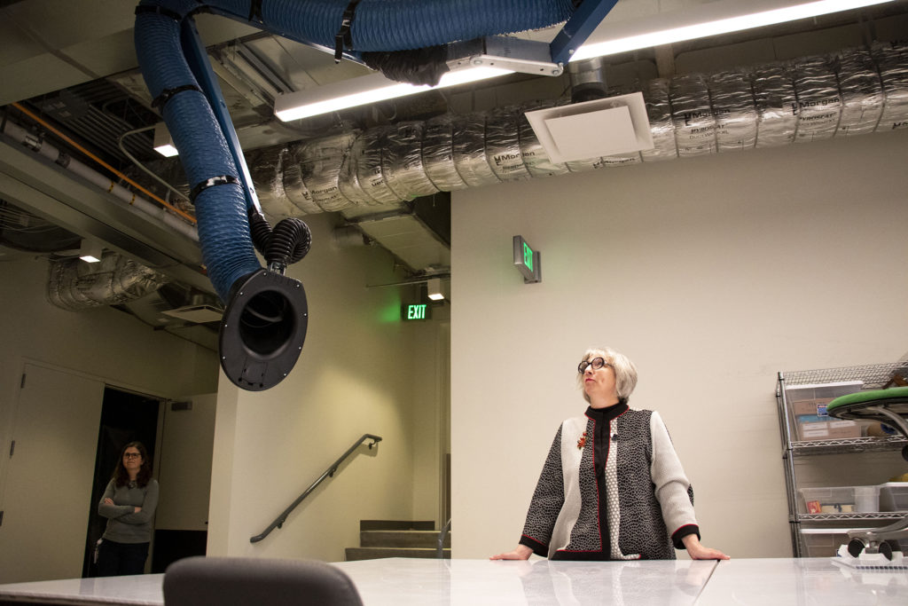 """Sarah Melching, the Denver Art Museum's director of conservation, peers up at a new """"trunk"""" (think elephant) exhaust system in the new restoration lab in the newly renovated Martin Building. Dec. 17, 2019. (Kevin J. Beaty/Denverite)"""