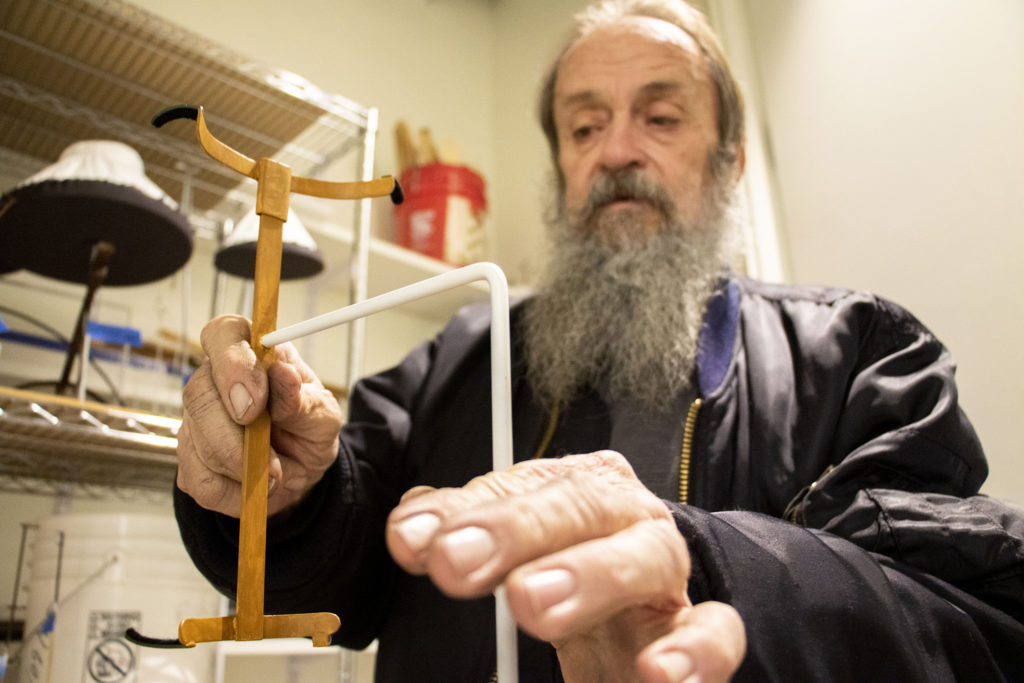 Steve Osborne, a 28-year veteran of the Denver Art Museum's conservation department, shows off one of his custom art mounts in the department's new lab. Dec. 17, 2019. (Kevin J. Beaty/Denverite)