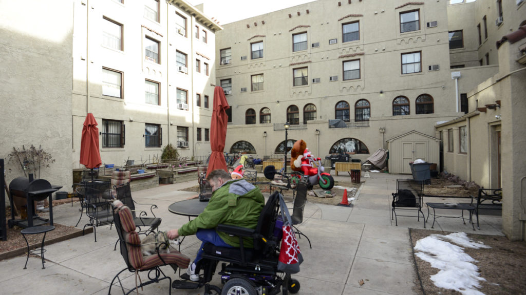 Randy Kilbourn sits with his dog Arlo on the patio of the Olin Hotel Apartments in Capitol Hill. (Lindsay Fendt/Denverite)