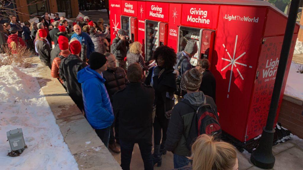 People gathered outside the Giving Machine at Writer Square on Monday, Dec. 2, in downtown Denver. (Esteban L. Hernandez/Denverite)