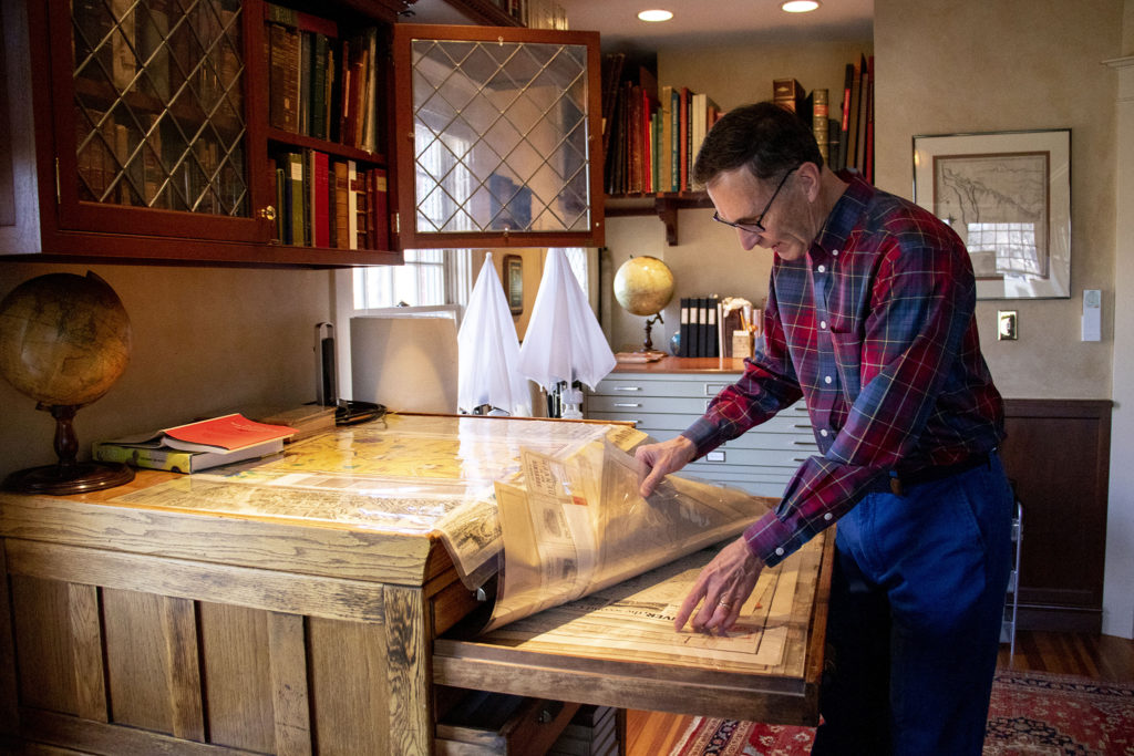Wesley Brown sorts through his map collection in one of two rooms dedicated to his passion in his South Park Hill home. Dec. 16, 2019. (Kevin J. Beaty/Denverite)