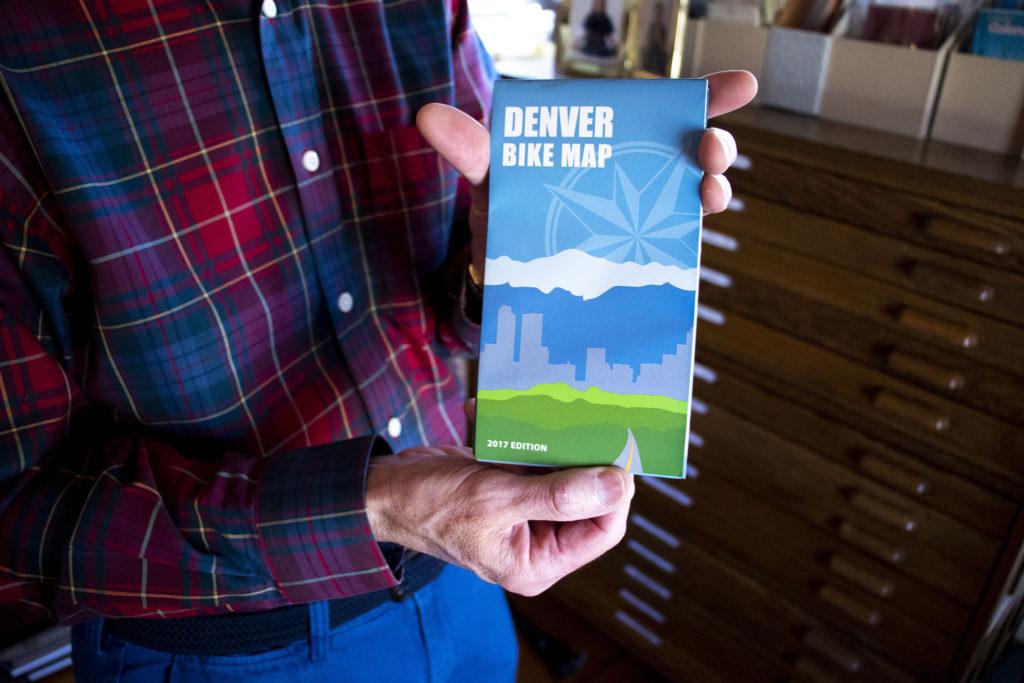 Wesley Brown holds a 2017 Denver Bike Map stored here in his map room. Dec. 16, 2019. (Kevin J. Beaty/Denverite)