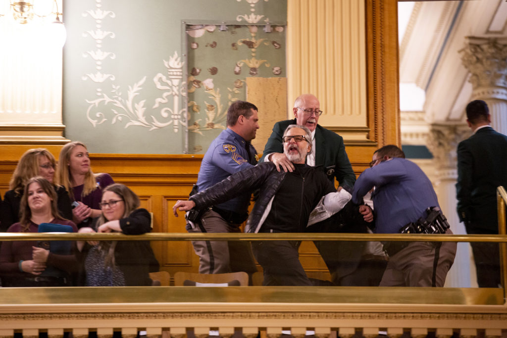 "An environmental protester is ejected from the House gallery after he burst in yelling, ""Ban fracking now!"" during Gov. Jared Polis' second State of the State address. Jan. 9, 2020. (Kevin J. Beaty/Denverite)"