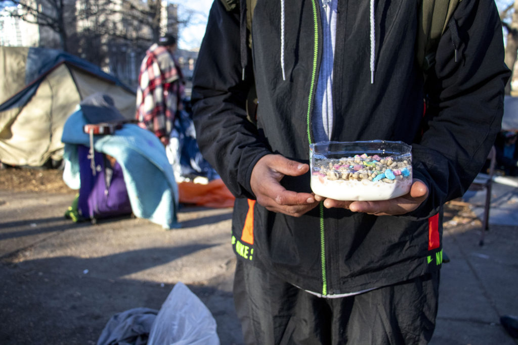 A man named Berto made a bowl of Lucky Charms before he packed his things and left Lincoln Memorial Park. Jan. 15, 2020. (Kevin J. Beaty/Denverite)