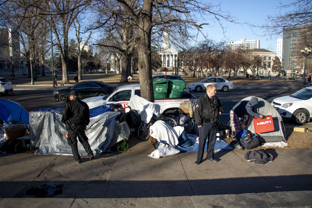 """Denver Department of Public Health and Environment workers break up an encampment at Lincoln Memorial Park due to a """"public health and safety risk,"""" Jan. 15, 2020. (Kevin J. Beaty/Denverite)"""