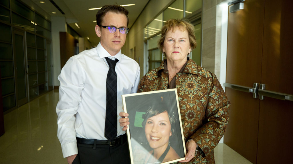 Teddy Bounds and Peggy Boardman hold pose for a portrait with a photo of Alexis Bounds, who was killed in an accident while on her bike. Jan. 24, 2020. (Kevin J. Beaty/Denverite)