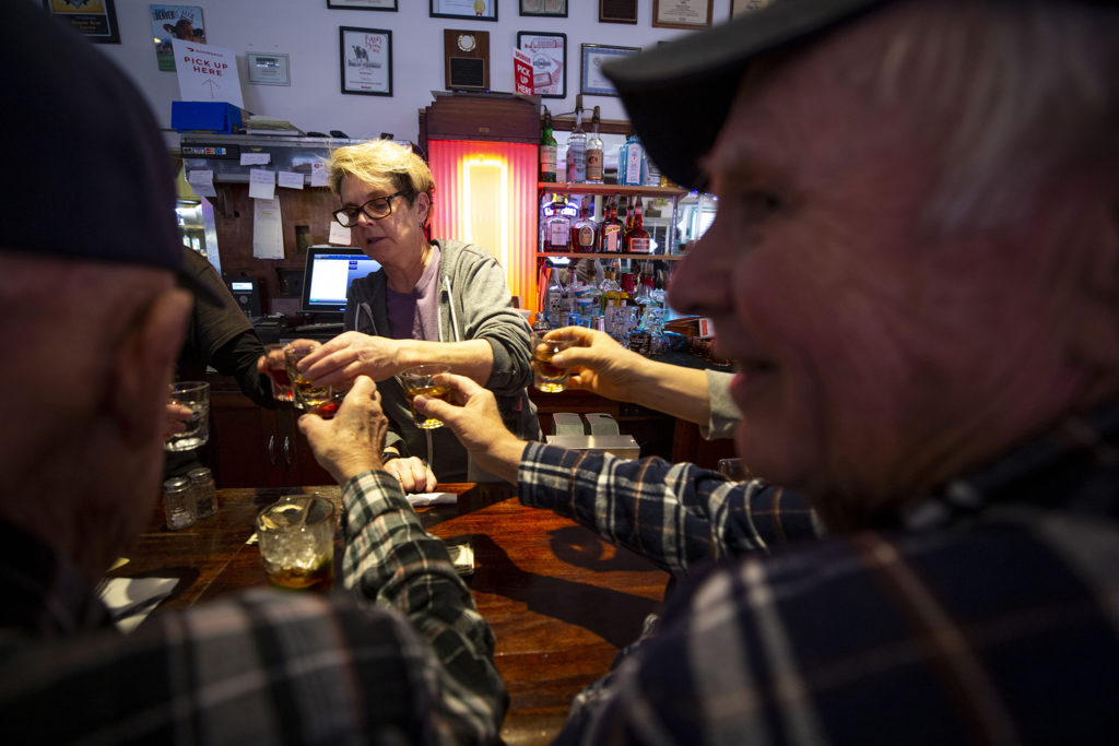 Linda Briggs serves a round of shots in honor of Marsha Kendrick, who died recently after battling alzheimers, at Bonnie Brae Tavern, Jan. 25, 2020. (Kevin J. Beaty/Denverite)