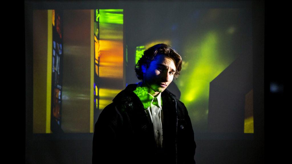 Myles Goldstein, Denver Jewish Film Festival entrant, poses for a portrait beneath a frame from his documentary inside a University of Denver media classroom. Jan. 28, 2020. (Kevin J. Beaty/Denverite)