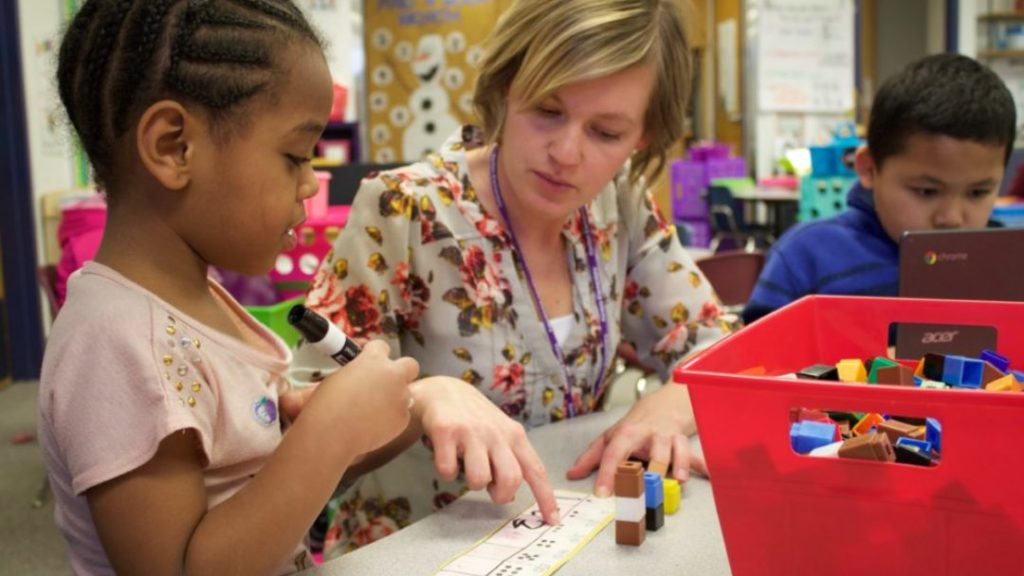 A kindergarten teacher at Kenton Elementary in Aurora helps a student practice saying and writing numbers. (Yesenia Robles/Chalkbeat)