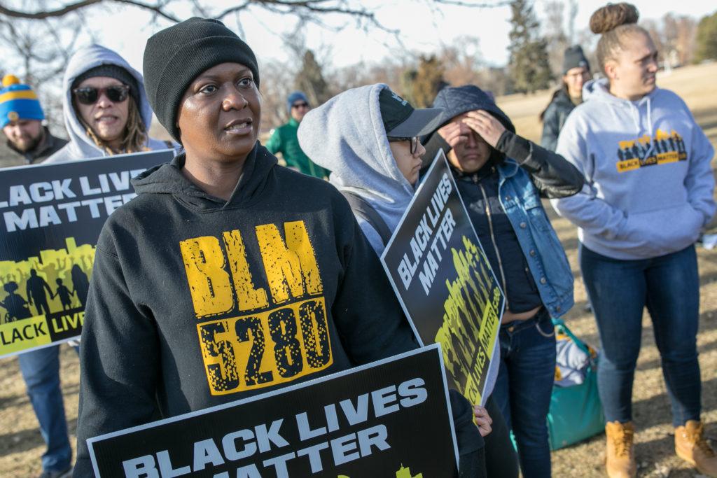 Apryl Alexander holds a Black Lives Matter sign, Jan. 20, 2020. (Hart Van Denberg/CPR News)