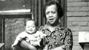 Photograph of Doctor Justina L Ford holding a baby while standing on a porch, 2825 High St., circa 1935. (Denver Public Library/Western History Collection)