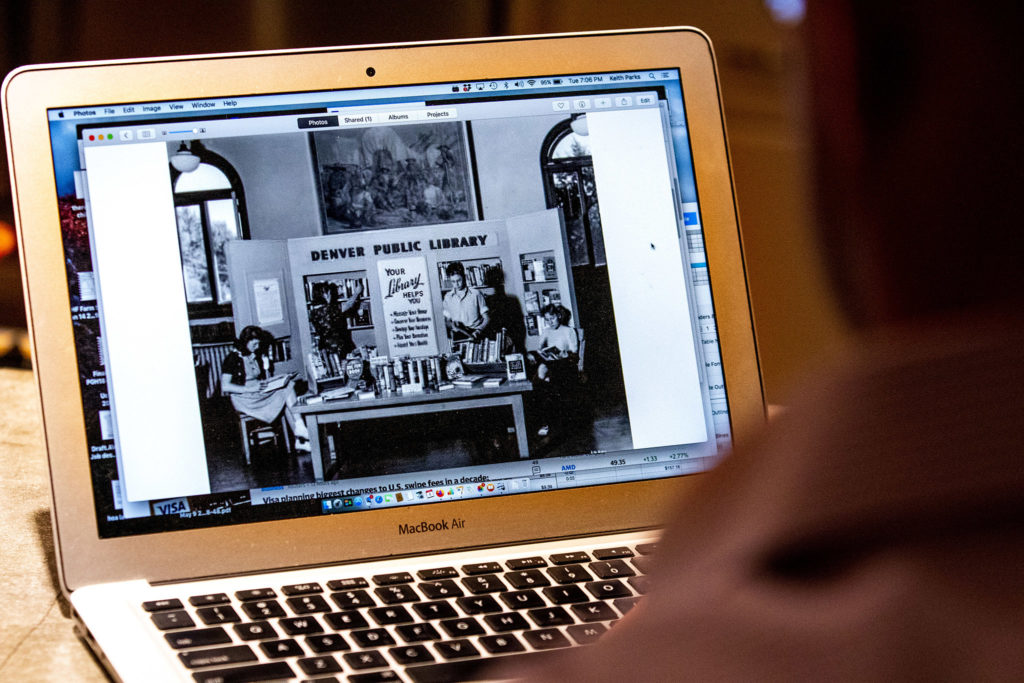 Keith Parks shows off some historic photos of the old Carnegie library that became his home in Denver's Cole neighborhood. Feb. 5, 2020. (Kevin J. Beaty/Denverite)