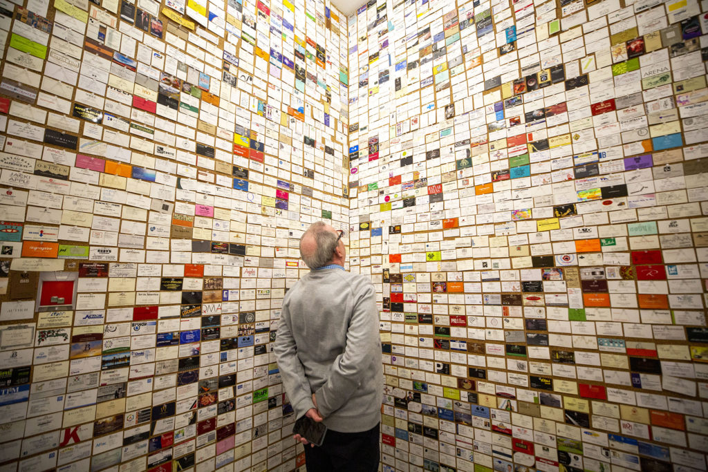Kevin Benjamin examines a wall full of business cards, part of Devon Dikeou's exhibition at her art space downtown, Feb. 20, 2020. (Kevin J. Beaty/Denverite)