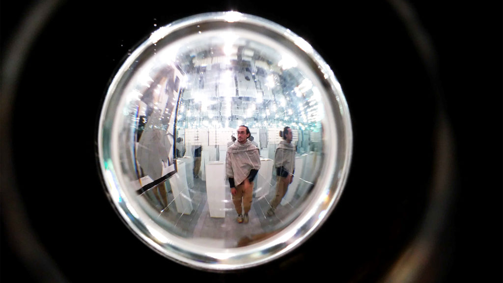 """A look through a peephole into a room of mirrors, part of Devon Dikeou's """"Mid-Career Smear"""" exhibition at her downtown art space. Feb. 20, 2020. (Kevin J. Beaty/Denverite)"""