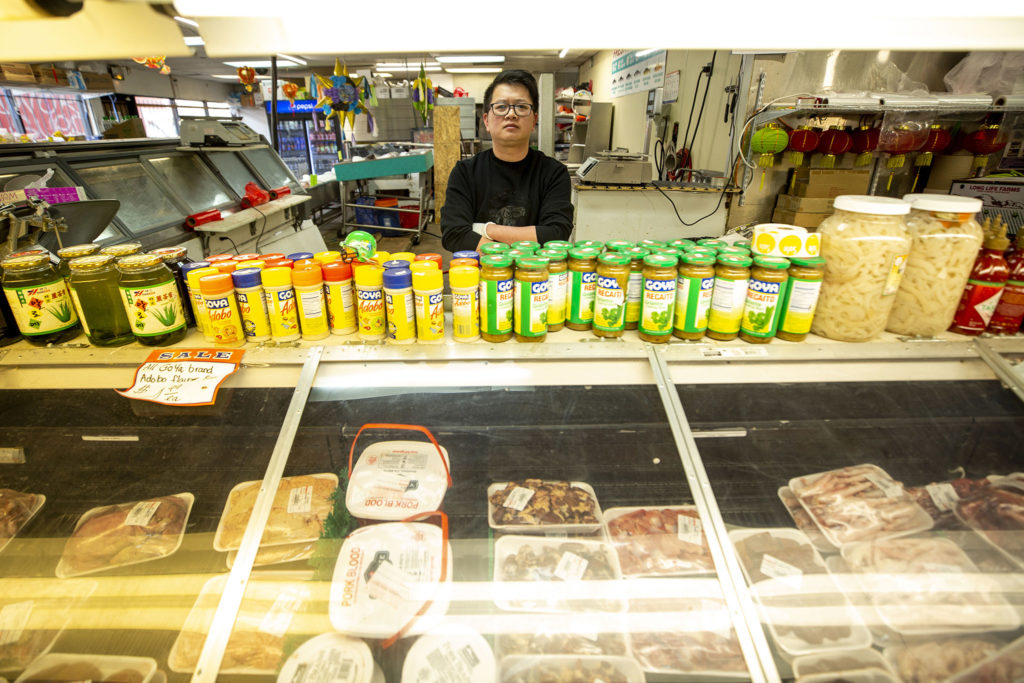 Ken Do, manager and owner at Little Saigon Market, poses behind the counter at his South Federal Boulevard grocery store. Feb. 25, 2020. (Kevin J. Beaty/Denverite)