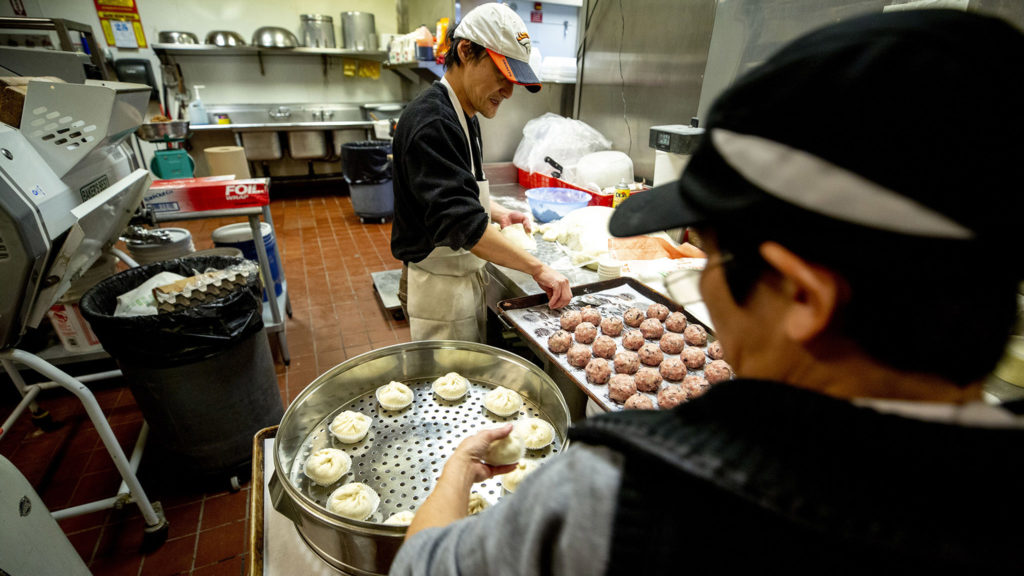 Wai Mo and a colleague roll sticky buns in the back of Pacific Ocean Marketplace, Feb. 25, 2020. (Kevin J. Beaty/Denverite)