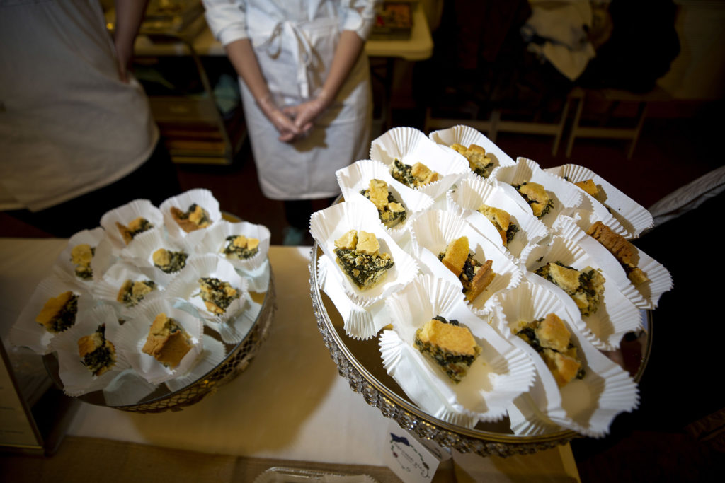 Some of Diana Rivero's spinach pies, on display at the booth for her business, Just Indulgence. A speed tasting event at the University of Denver's Schiol of Social Work. Feb. 25, 2020. (Kevin J. Beaty/Denverite)
