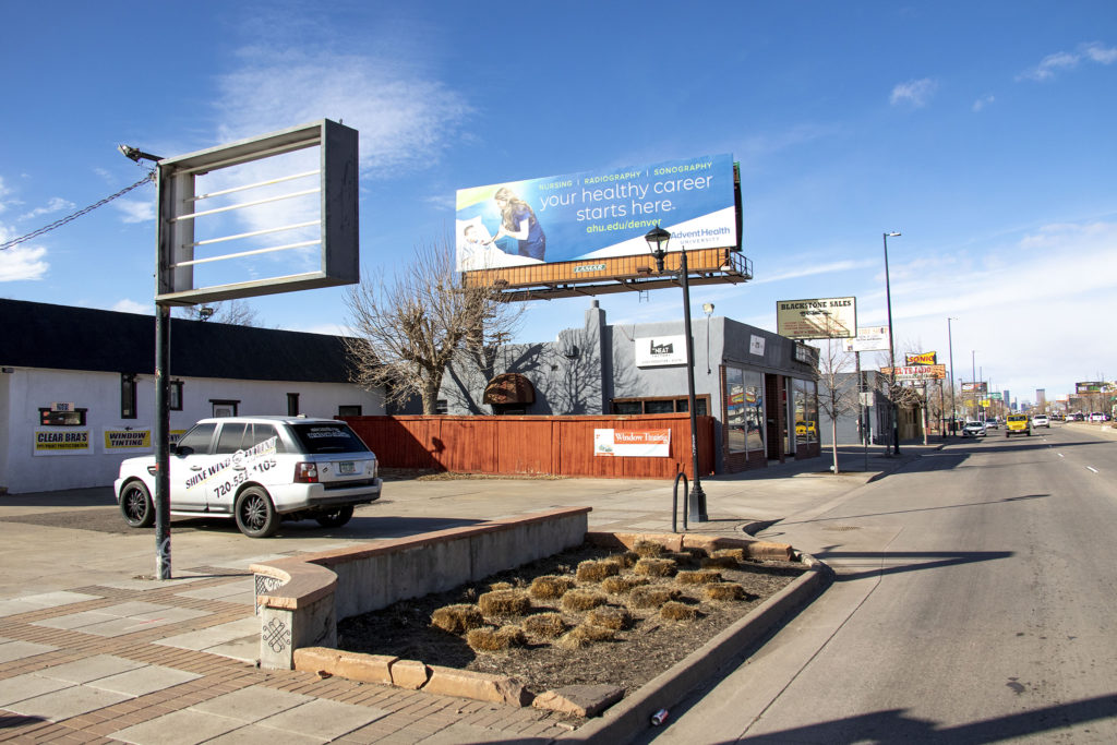 A strip of businesses in Overland that a develper hopes to rezone for five-story buildings. Feb. 27, 2020. (Kevin J. Beaty/Denverite)