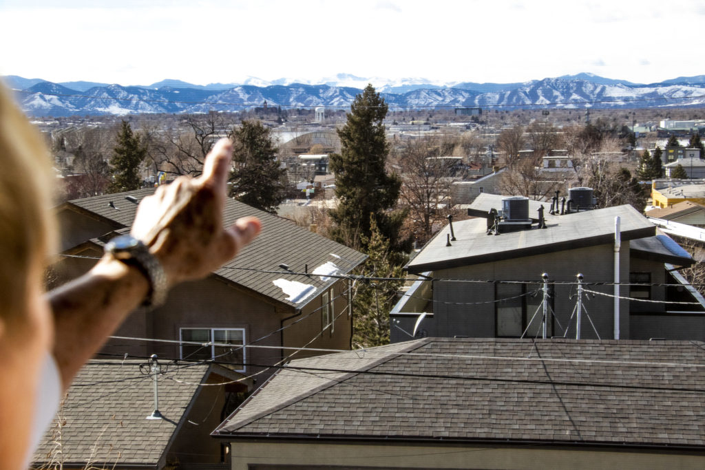 Sandy Pierce looks out onto the view from her home in Denver's Rosedale neighborhood. Feb. 27. 2020.  (Kevin J. Beaty/Denverite)