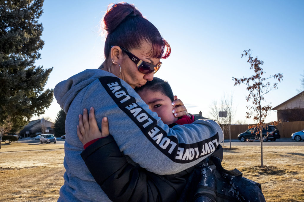 Christina Zaldivar comforts her youngest son, Francysco, as she drops him off at school. His father will be deported soon, and she's leaving this morning for Mexico to meet him. Jan. 9, 2020. (Kevin J. Beaty/Denverite)