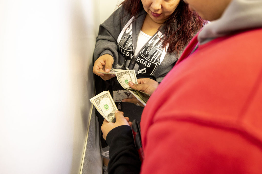 Christina Zaldivar gives her son, Diego, some money as she drops him off at Sunday school. March 7, 2020. (Kevin J. Beaty/Denverite)