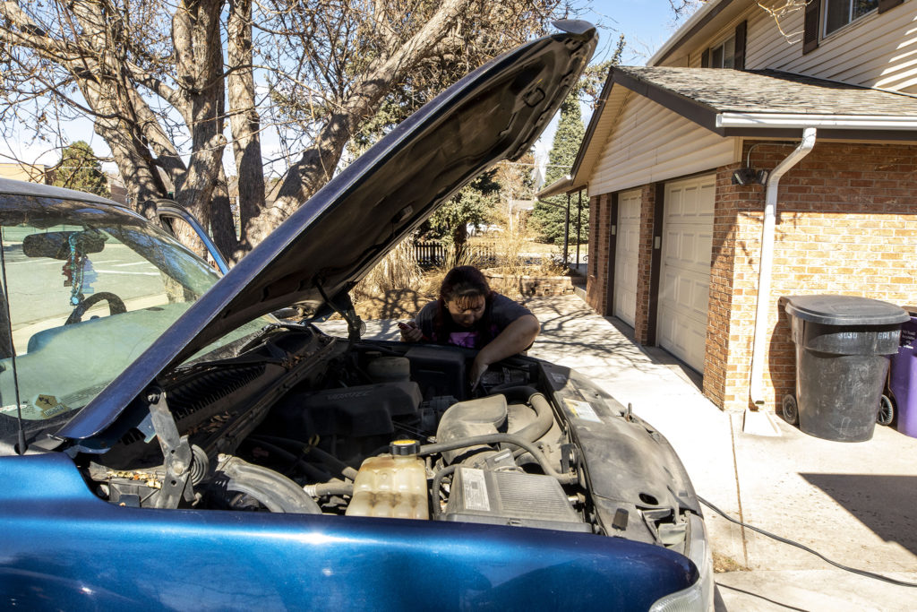 Christina Zaldivar works on a dead car battery in her driveway. March 7, 2020. (Kevin J. Beaty/Denverite)