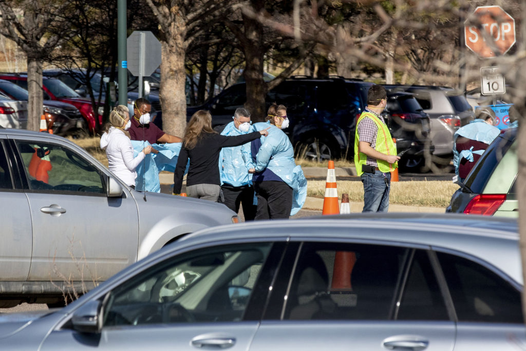 Workers don scrubs as people line up in cars for testing at the Colorado Department of Health and Environment's COVID-19 testing station in Lowry. March 11, 2020. (Kevin J. Beaty/Denverite)