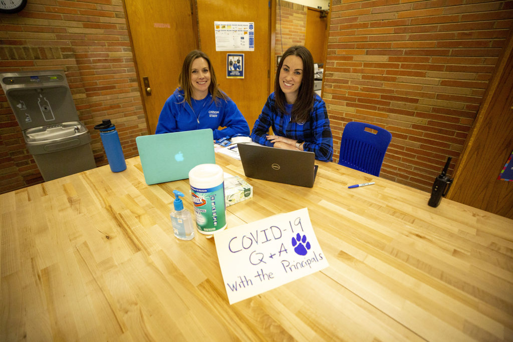 """Carson Elementary Principal Anne Larkin and Principal Intern Corey Jenks sit at the """"COVID-19 Q&A"""" table by the main office. March 13, 2020. (Kevin J. Beaty/Denverite)"""