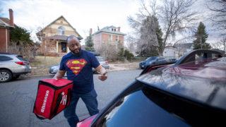 Julian Rai drops off a Grubhub order on a Friday evening. March 13, 2020. (Kevin J. Beaty/Denverite)